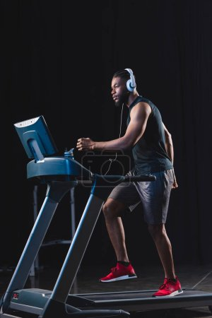 side view of handsome young african american sportsman in headphones running on treadmill