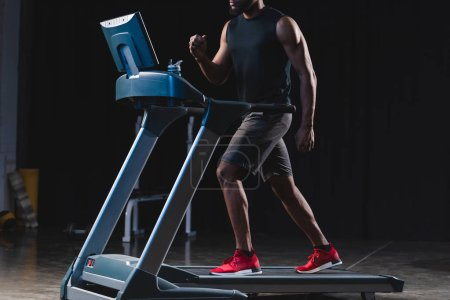 cropped shot of young african american sportsman training on treadmill