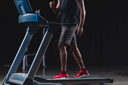 cropped shot of african american man in earphones training on treadmill