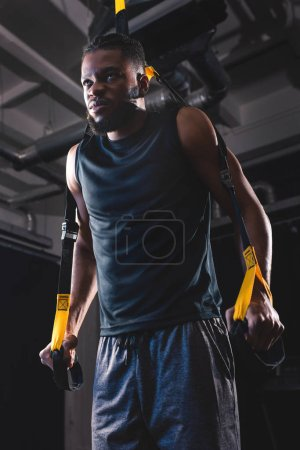 low angle view of athletic african american man training with fitness straps