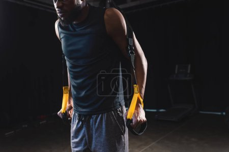 Photo for Cropped shot of muscular african american sportsman training with fitness straps - Royalty Free Image