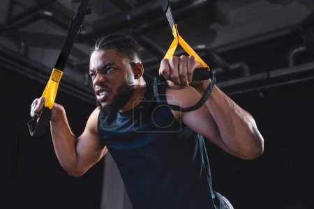 low angle view of muscular african american sportsman training with fitness straps