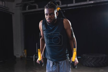 muscular african american sportsman training with suspension straps