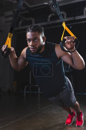 focused young african american sportsman exercising with resistance bands
