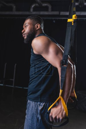 side view of muscular african american man looking away while training with suspension straps