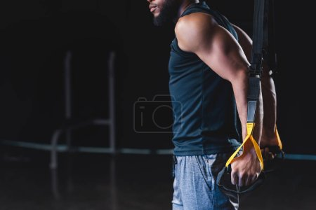 side view of muscular african american sportsman exercising with resistance bands