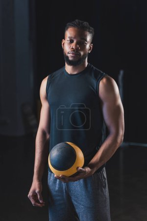 handsome young african american sportsman holding ball and looking at camera