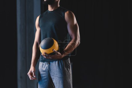 cropped shot of muscular african american man in sportswear holding ball