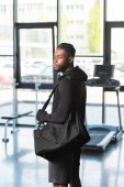 handsome athletic african american man in sportswear holding bag and looking away in gym