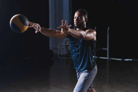 muscular african american sportsman training with ball in gym