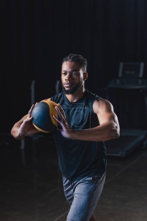 muscular african american sportsman holding ball while exercising in gym