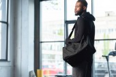 handsome african american man in sportswear holding bag and looking away in gym