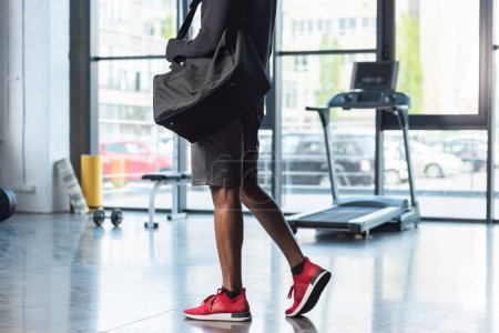 cropped shot of african american man in sportswear holding bag in gym