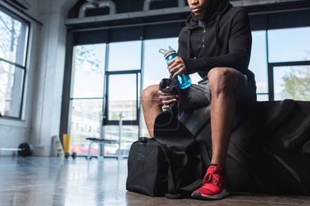 cropped shot of young african american sportsman holding bottle of water and towel while sitting in tyre in gym