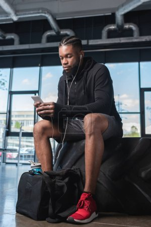 young african american man in earphones sitting in tyre and using smartphone in gym