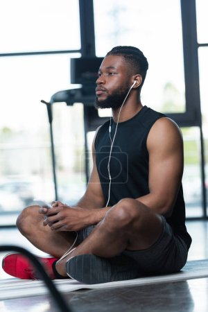 pensive african american sportsman in earphones using smartphone and looking away while sitting on yoga mat in gym