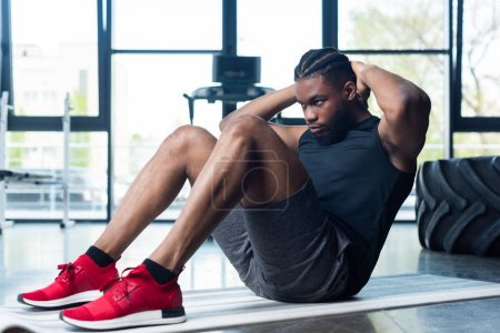 athletic young african american man doing abs and looking away in gym