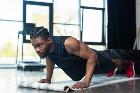 muscular african american sportsman doing push ups and looking away in gym