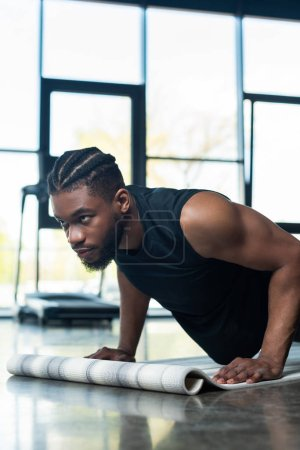 focused muscular african american man doing push ups in gym