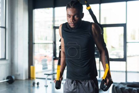 muscular young african american sportsman exercising with resistance bands in gym