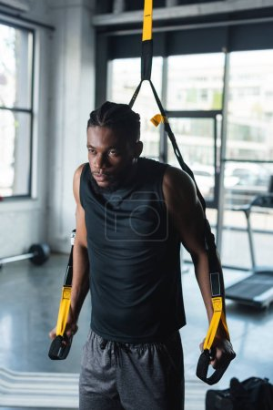 serious young african american sportsman training with fitness straps in gym