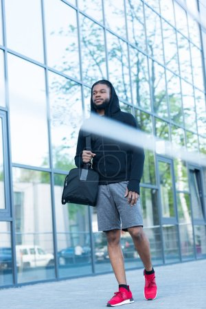 low angle view of young african american man in sportswear walking with bag on street