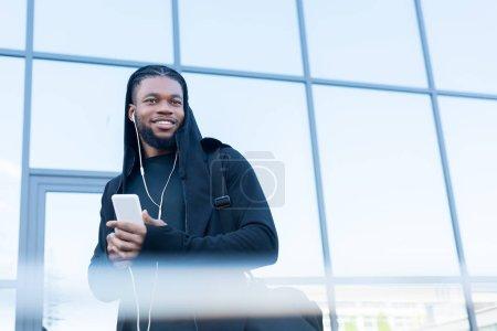 selective focus of handsome smiling african american man in earphones using smartphone on street