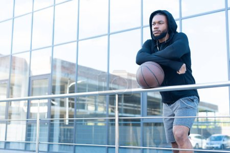pensive african american man in earphones leaning at railings with basketball ball and looking away