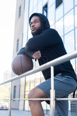 pensive african american man leaning at basketball ball and looking away on street