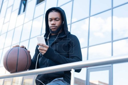 low angle view of sportive african american man in earphones using smartphone while standing with basketball ball on street
