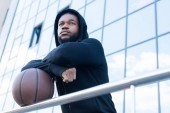 low angle view of pensive african american sportsman looking away while standing with basketball ball on street
