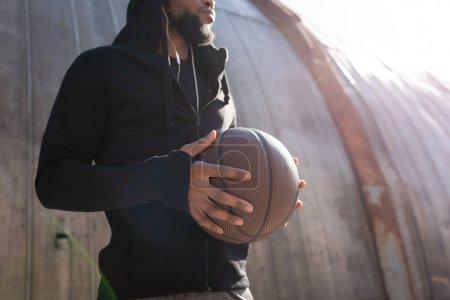 Photo pour Plan recadré d'un homme afro-américain tenant un ballon de basket dans la rue - image libre de droit