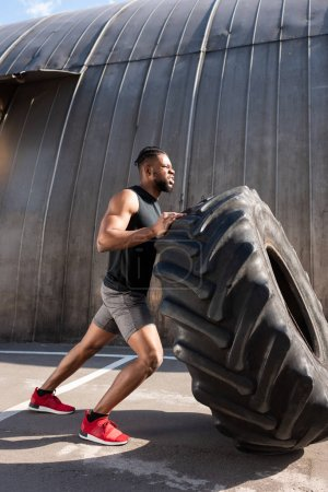 athletic african american man exercising with tire on street
