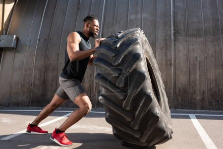muscular african american sportsman exercising with tire on street