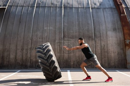 Photo for Side view of athletic african american man exercising with tire on street - Royalty Free Image