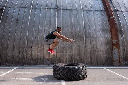 muscular african american sportsman jumping while training with tyre on street