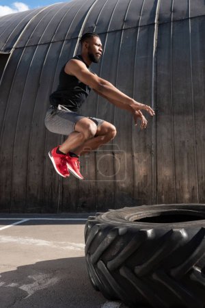 side view of muscular african american man jumping while training with tyre on street