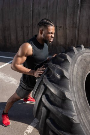 high angle view of muscular african american man exercising with tyre on street
