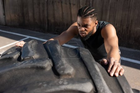 high angle view of sportive african american man training with tire on street