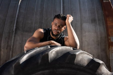 handsome young african american sportsman leaning at tyre and looking at camera