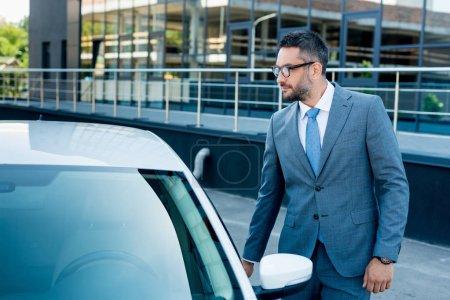 businessman in eyeglasses opening car door on street