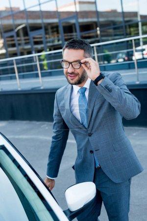 smiling businessman in eyeglasses opening car door on street