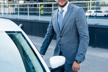 cropped shot of businessman standing near car on parking