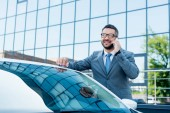 portrait of smiling businessman talking on smartphone while standing at car on street