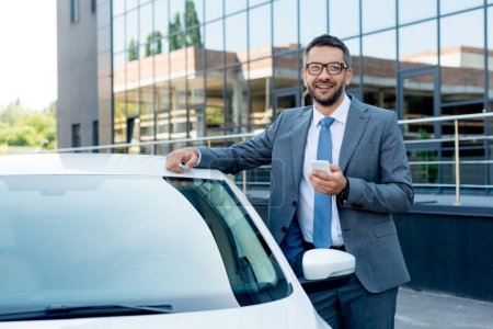 portrait of smiling businessman with smartphone standing at car on street