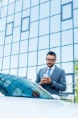 portrait of businessman using smartphone while standing at car on street