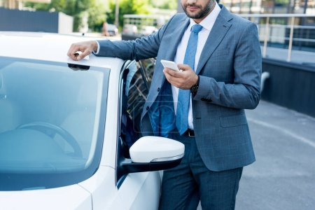 partial view of businessman using smartphone while standing at car on street
