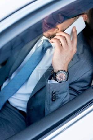 partial view of smiling businessman in eyeglasses talking on smartphone while driving car