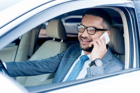 smiling businessman talking on smartphone while driving car
