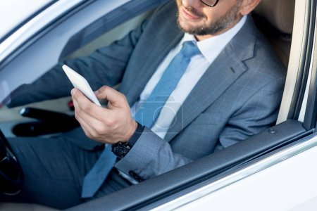 cropped shot of businessman using smartphone while driving car